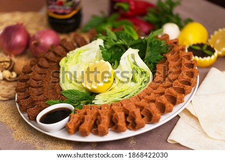 """Cig kofte, a raw meat dish in Turkish and Armenian cuisines. Turkish cig means """"raw"""" and kofte means meatball Turkish food raw cigkofte roll on wooden and black background Turkish food"""