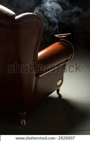 Cigar and beautiful leather armchair on marble to a floor