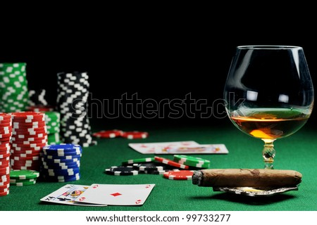 Cigar, chips for gambling, drink and playing cards on green