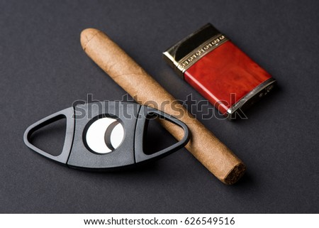 Cigar, lighter and ? cigar cutter laying on a dark background
