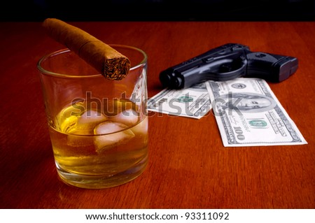 Cigar on the whiskey and two hundred Dollars bills under handgun