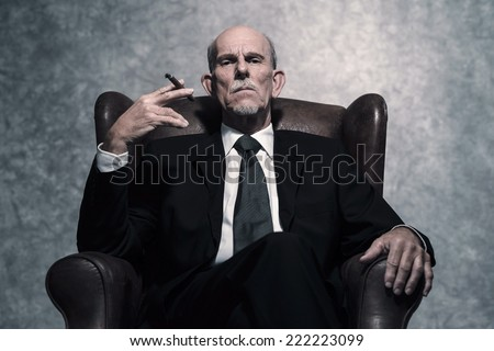 Cigar smoking senior businessman with gray beard wearing dark suit and tie. Sitting in leather chair. Against grey wall.