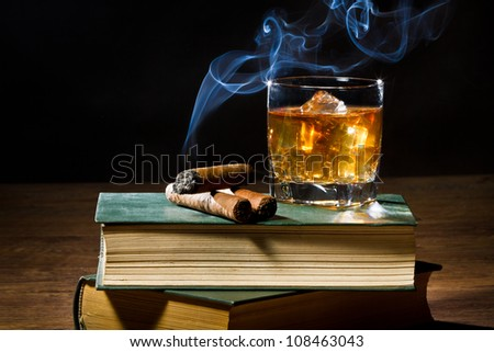 Cigar with smoke and whisky on ice in library