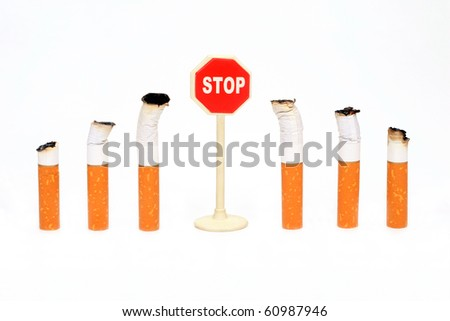 "Cigaret butts stand round a sign ""Stop"" on a white background"