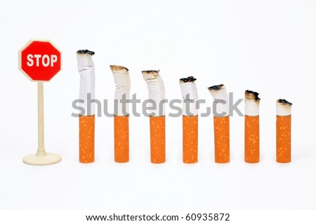 "Cigaret stubs standing in a row before a sign ""Stop"" on a white background"