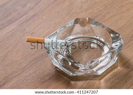 cigarette and a glass ashtray on an old wooden table #411247207