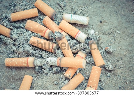 Cigarette burning in outdoors ashtray with sand closeup