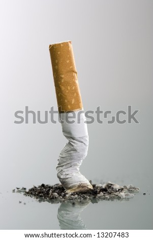 Cigarette butt end crushed into ashtray - grey background