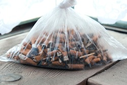 Cigarette butts in a plastic bag. The problem of humanity. Smoking cigarettes, bad habit. Nicotine addiction. Garbage