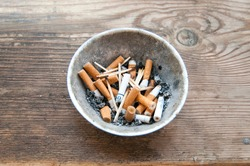 Cigarette butts in an ashtray on a wooden background. The problem of humanity. Smoking cigarettes, bad habit. Nicotine addiction. Garbage.