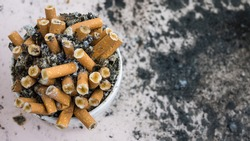 cigarette butts in an ashtray top view with ashes in the background