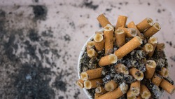 cigarette butts in an ashtray with ashes in the background