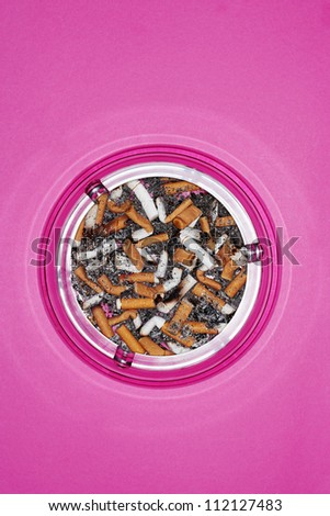 Cigarette butts in ashtray over pink background