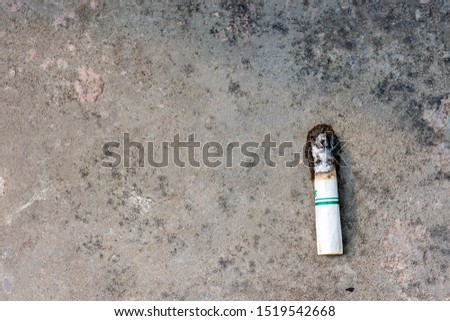 Cigarette butts left Was left on the concrete road surface #1519542668