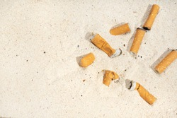 Cigarette butts on sand at the beach
