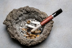 Cigarette holder and cigarette butts in an old dirty volcanic lava ashtray. Close-up. Selective focus.