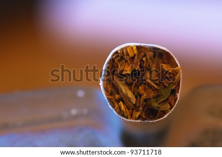 Cigarette in ashtray. High magnification macro shot.
