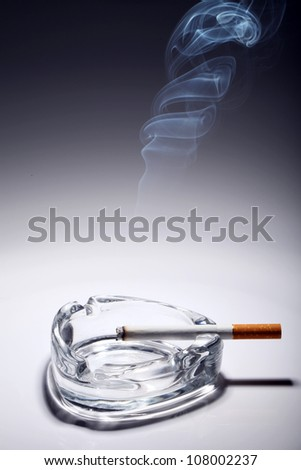 Cigarette in the ashtray over gray gradient