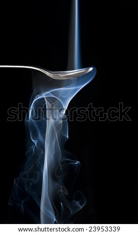 Cigarette smoke, and a spoon with black background
