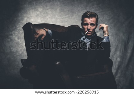 Cigarette smoking retro fifties cool business fashion man wearing black suit. Sitting in leather chair. Gray wall.