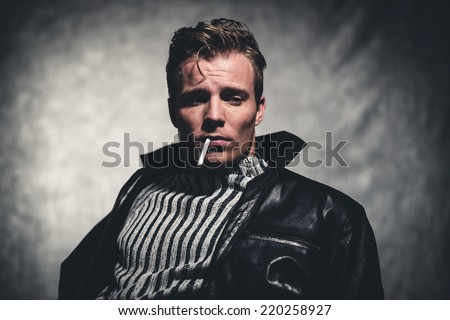 Cigarette smoking retro fifties cool rebellion fashion man wearing striped woolen sweater and black leather jacket. Gray wall.