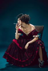 Cigarette smoking. Young woman as Anna Karenina isolated on dark blue background. Retro style, comparison of eras concept. Beautiful female model like literature character, great, old-fashioned.