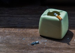 Cigarette that were burning placed on greyish green ashtray on old wooden rustic table. Copy space, No focus, specifically.