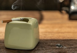 Cigarette that were burning with billowing smoke were placed on an ancient green ceramic ashtray on old wooden rustic table. Copy space, No focus, specifically.