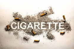 Cigarette word text written in ash filth or dirt with orange cigarette butts around as smoking passion, health danger, nicotine lust, sickness and illness concept background