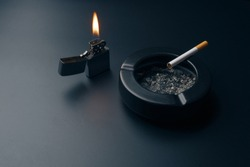 cigarettes, chrome lighter with flame and black ceramic ashtray full of ashes on the black table