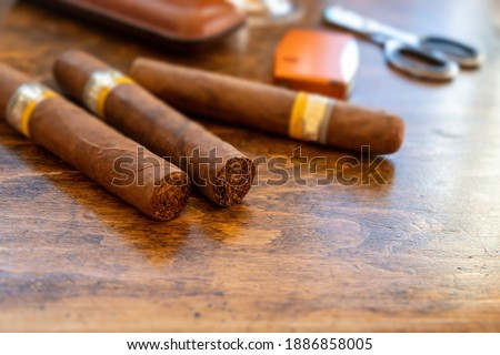 Cigars and accessories on a wooden office desk, closeup view. Cuban quality cigar tobacco smoking luxury lifestyle. Foto stock ©