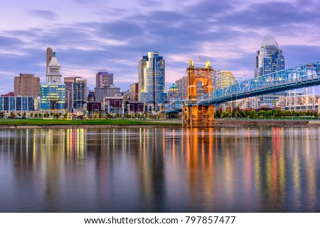 Cincinnati, Ohio, USA downtown skyline and bridge on the river at dusk.