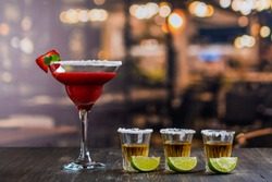 Cinco de Mayo celebration background. 5th May Mexican party. Strawberry mojito and tequila shots with lime on wooden table