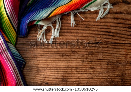Cinco de mayo fiesta party and indigenous cultures of Mexico concept theme with a Mexican rug called a serape isolated on wood background with copy space #1350610295