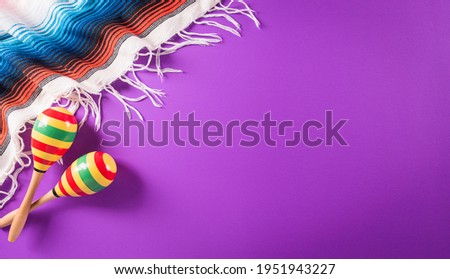 Cinco de Mayo holiday background made from maracas, mexican blanket stripes or poncho serape on purple background. Foto stock ©