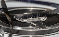 Cine film unrolling from reel.  old Super 8 footage with reel flat on table showing close up of film.  Vintage film making with scratches and dust in a clear spool holder.