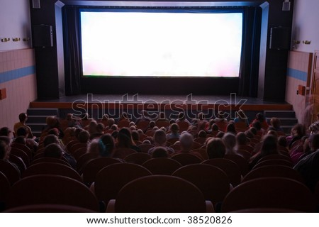 Cinema auditorium with people in chairs watching movie performance. Ready for adding your own picture.