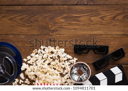 Cinema background, top view. Clapperboard, popcorn, soda and 3D glasses on wooden table, copy space. Movie goers accessories, cinematography concept #1094811701