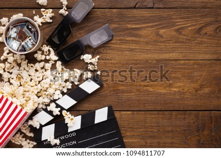 Cinema background, top view. Clapperboard, popcorn, soda and 3D glasses on wooden table, copy space. Movie goers accessories, cinematography concept #1094811707