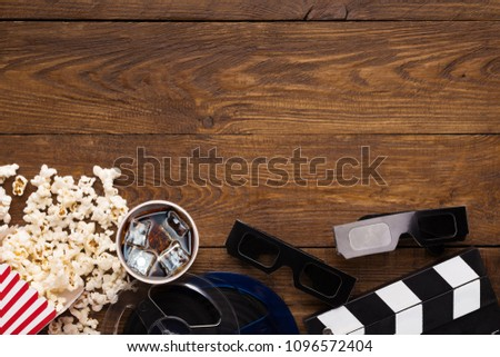 Cinema background, top view. Clapperboard, popcorn, soda and 3D glasses on wooden table, copy space. Movie goers accessories, cinematography concept #1096572404