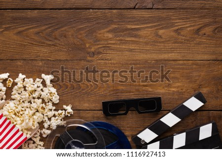 Cinema background, top view. Clapperboard, popcorn, soda and 3D glasses on wooden table, copy space. Movie goers accessories, cinematography concept #1116927413