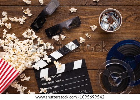 Cinema background, top view. Clapperboard, popcorn, soda and 3D glasses on wooden table. Movie goers accessories, cinematography concept #1095699542