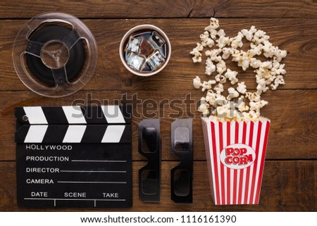 Cinema background, top view. Clapperboard, popcorn, soda and 3D glasses on wooden table. Movie goers accessories, cinematography concept, flat lay #1116161390