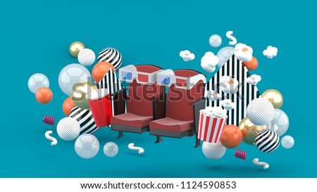 Stock Photo Cinema chair Soft drinks and popcorn among the colorful balls on the blue background.-3d rendering.