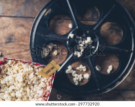 Cinema concept with vintage film reel, popcorn and a movie ticket