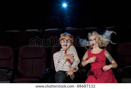 Cinema date, shocked couple is watching a scary movie
