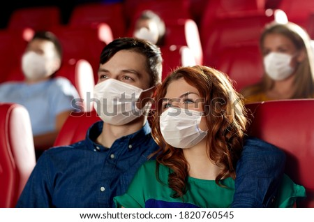 cinema, entertainment and pandemic concept - couple wearing face protective medical masks for protection from virus disease watching movie in theater