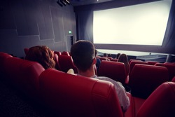 cinema, entertainment, leisure and people concept - couple watching movie in theater from back