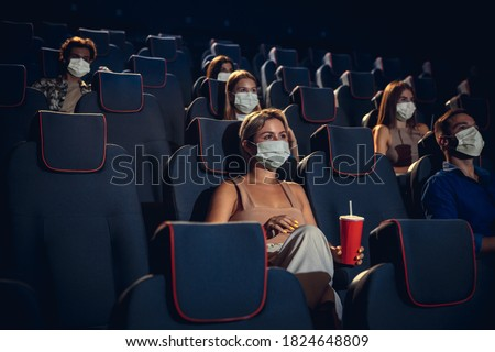 Cinema in quarantine. Coronavirus pandemic safety rules, social distance during movie watching. Men, women in protective face mask sitting in a rows of auditorium. Leisure time, youth culture concept.