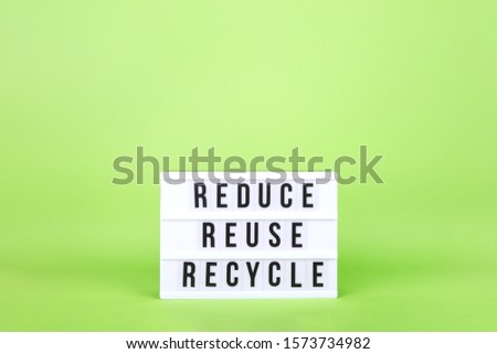 Cinema lightbox showing Reduce, Reuse, Recycle text on the light green drop. Place for text